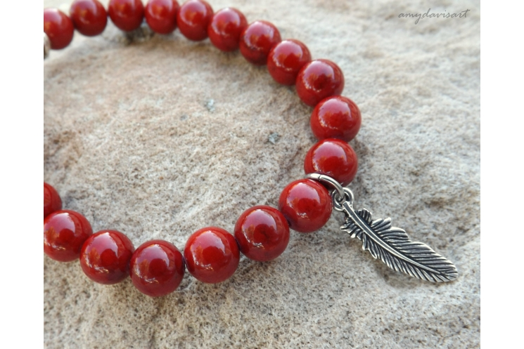 Red beaded bracelet with feather charm